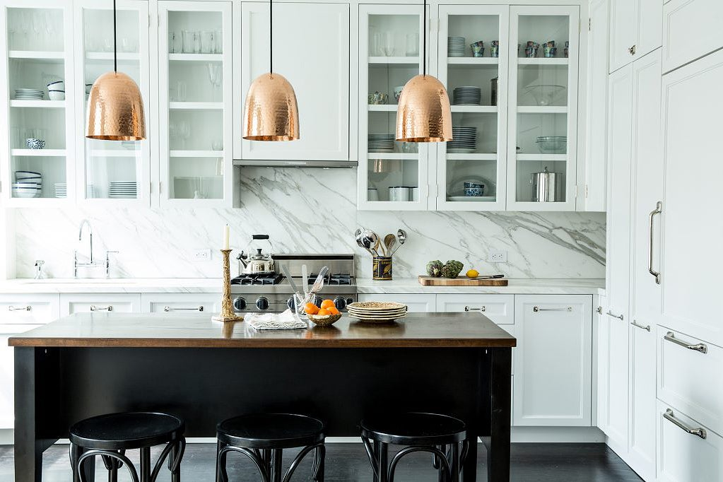 white kitchen with copper pendant lights over black island