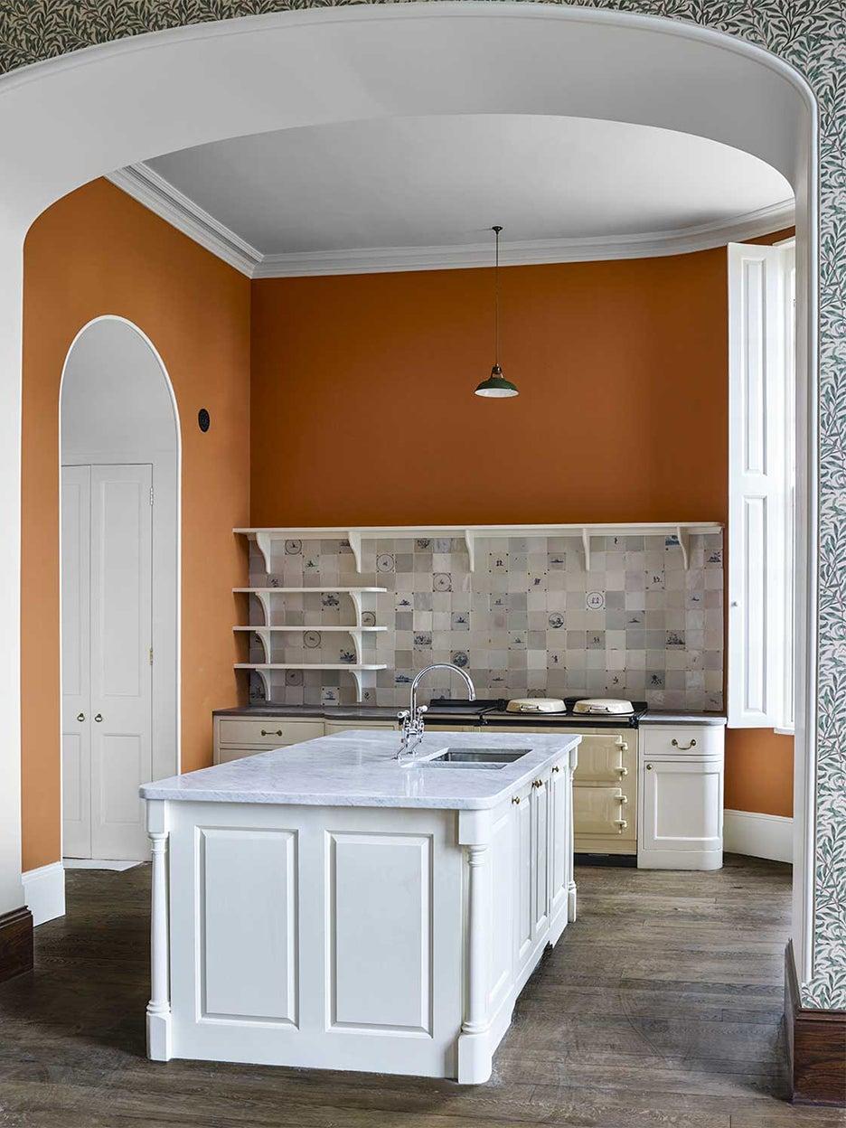 orange kitchen with white cabinets