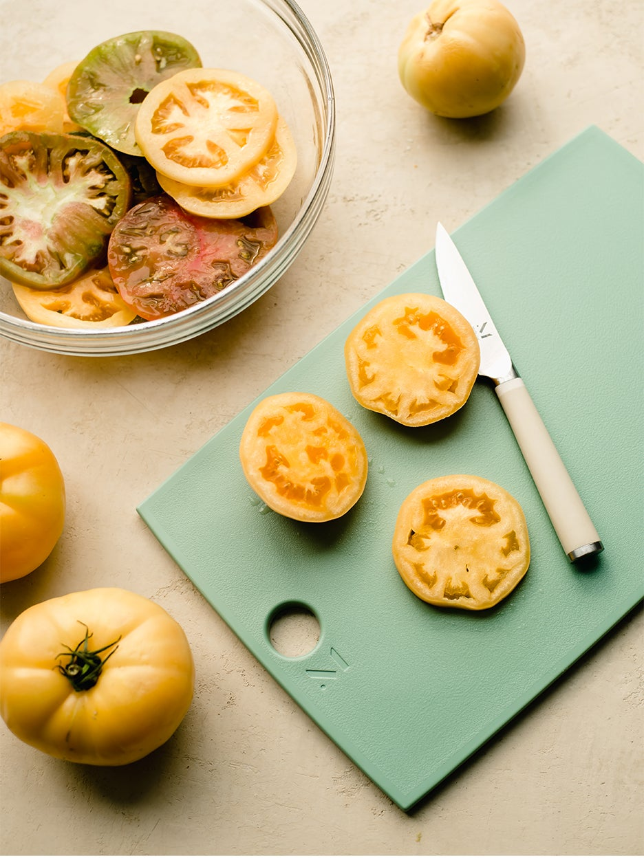 mint green cutting board with yellow tomatoes on top