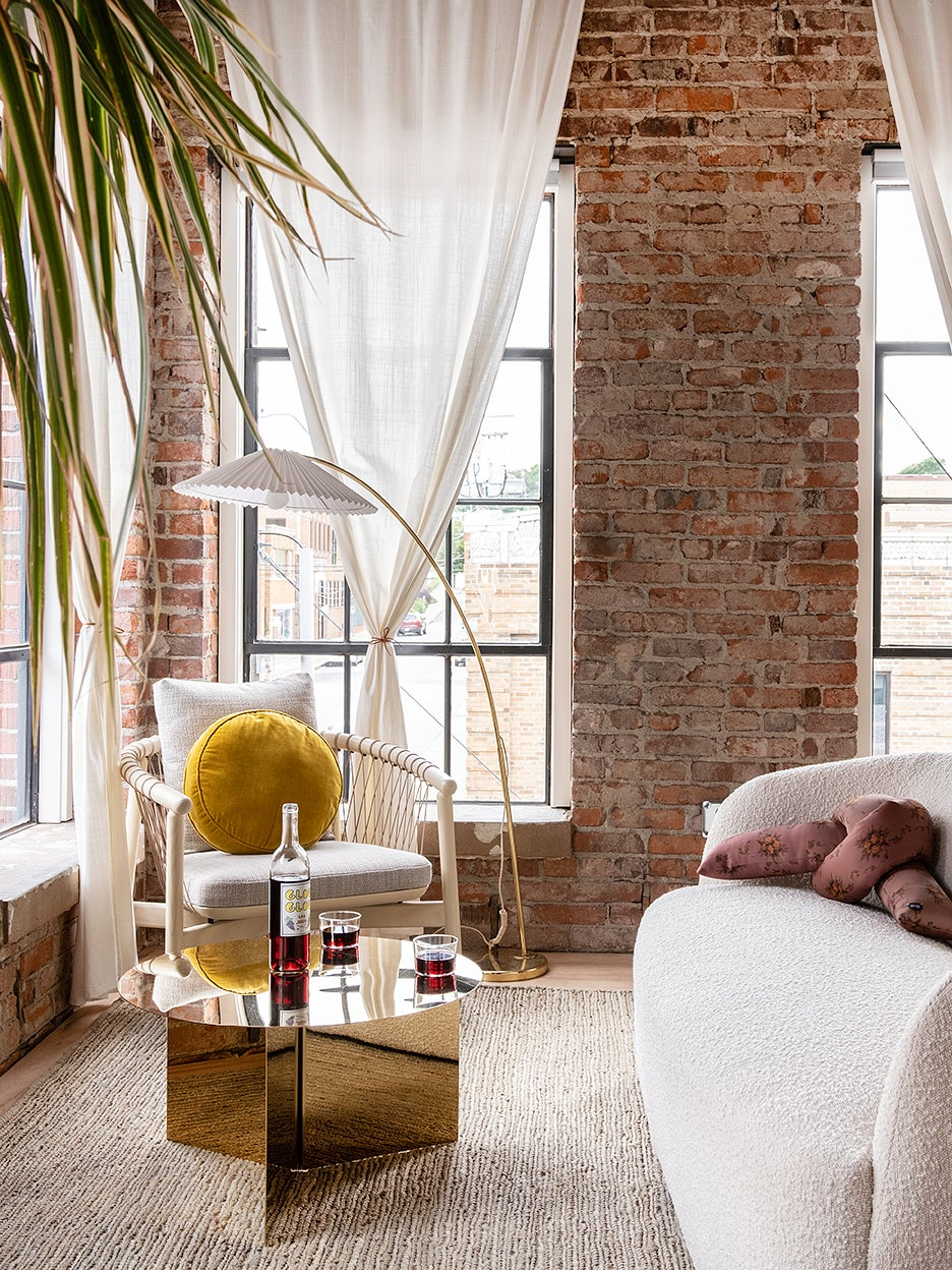 room with brick wall and white chair