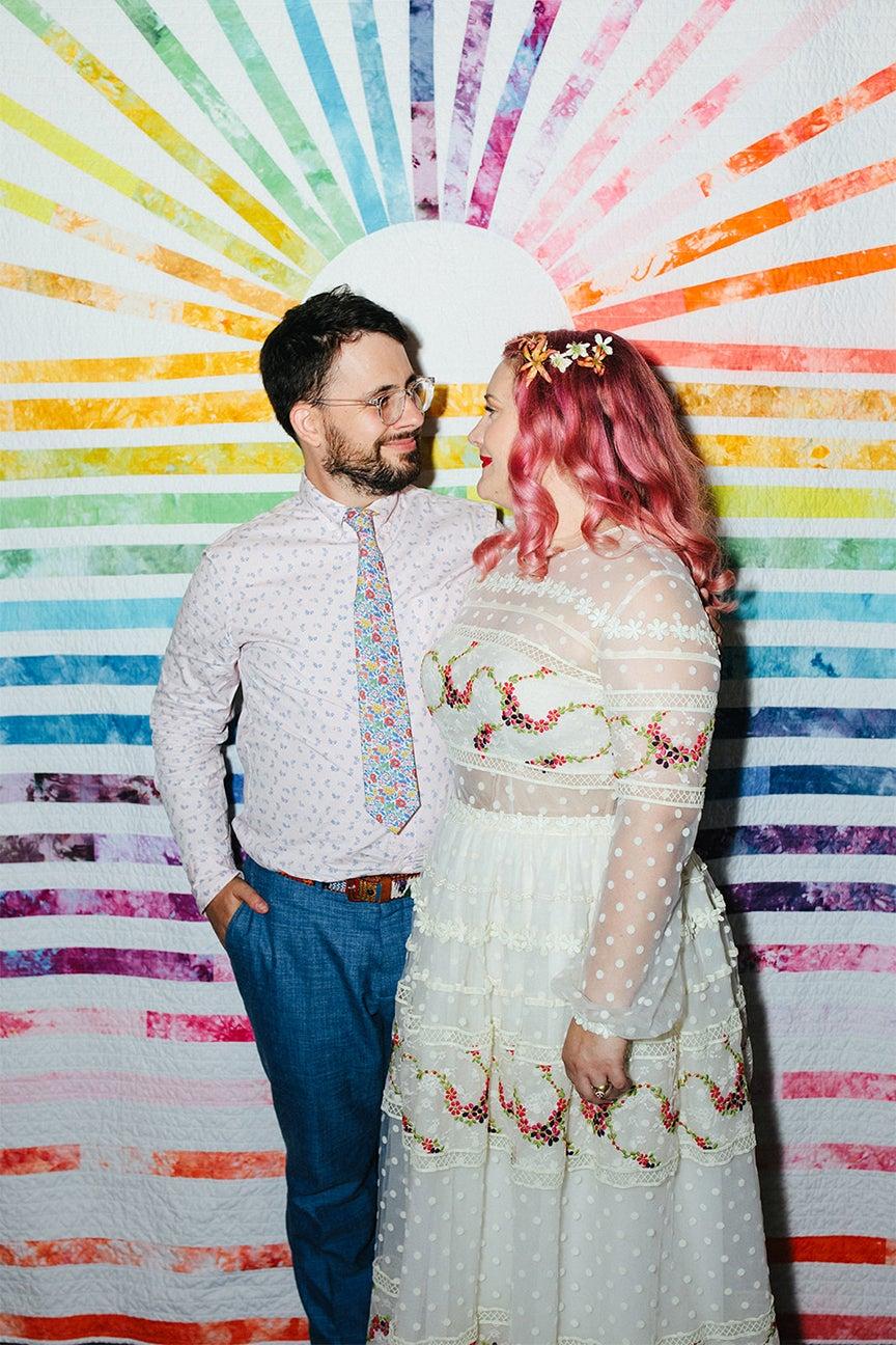 couple with rainbow sunburst backdrop
