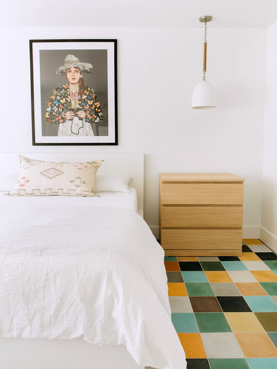 white bed with colorful floor tiles