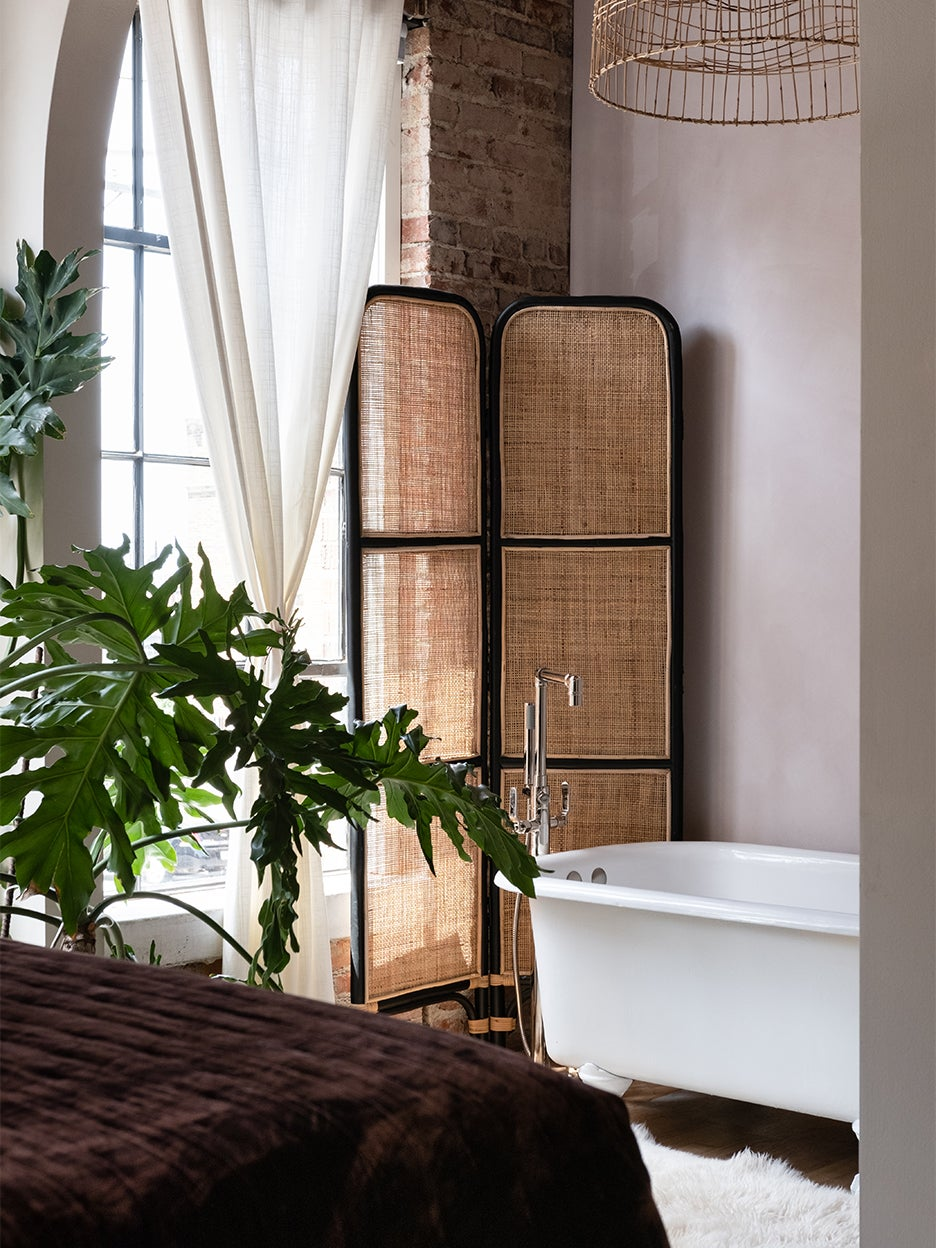 white clawfoot bathtub in front of cane room divider