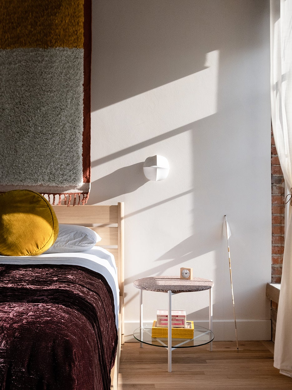 bedroom with purple bed spread and white sconce