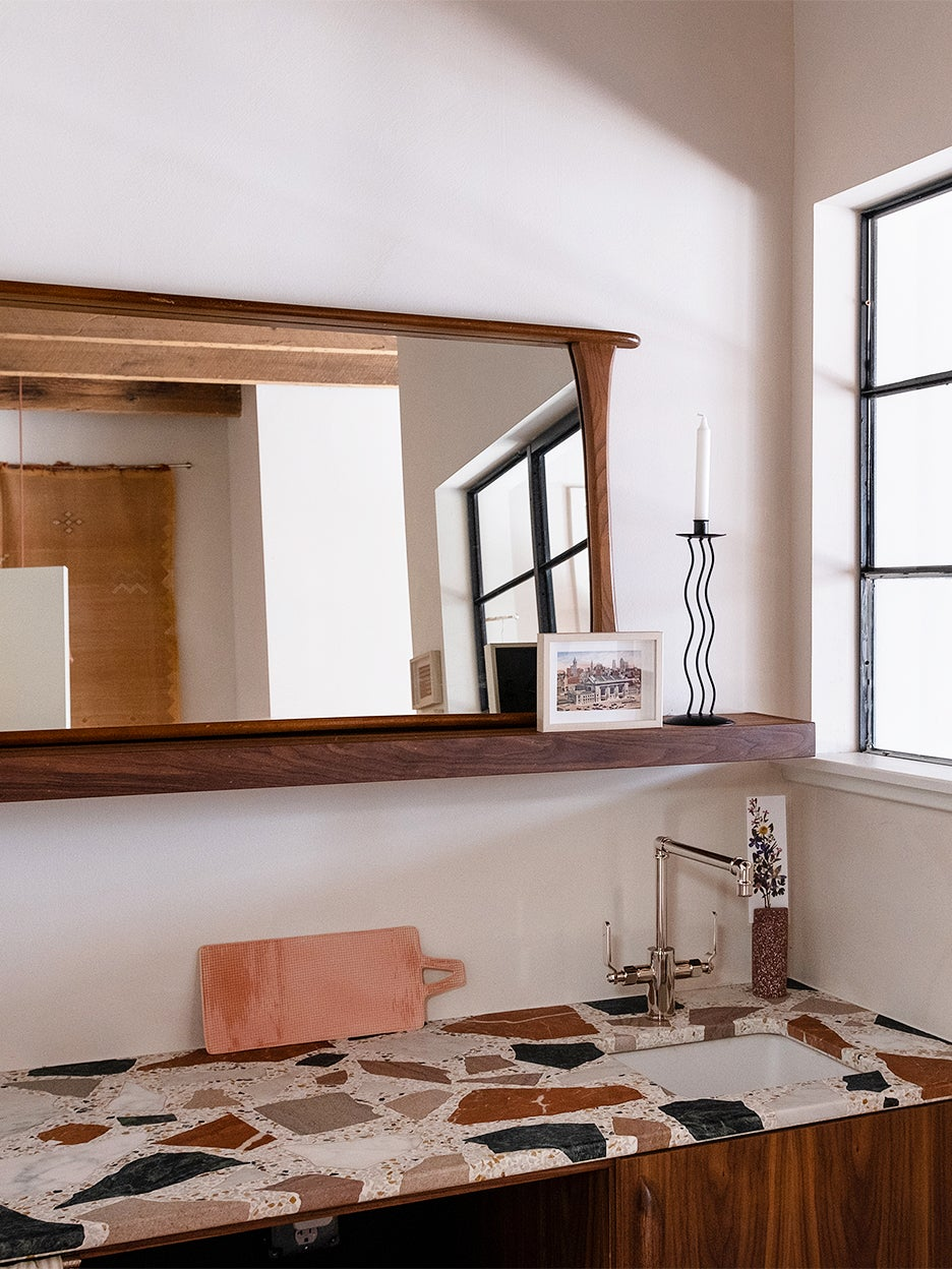 terrazzo counter in kitchenette below mirror
