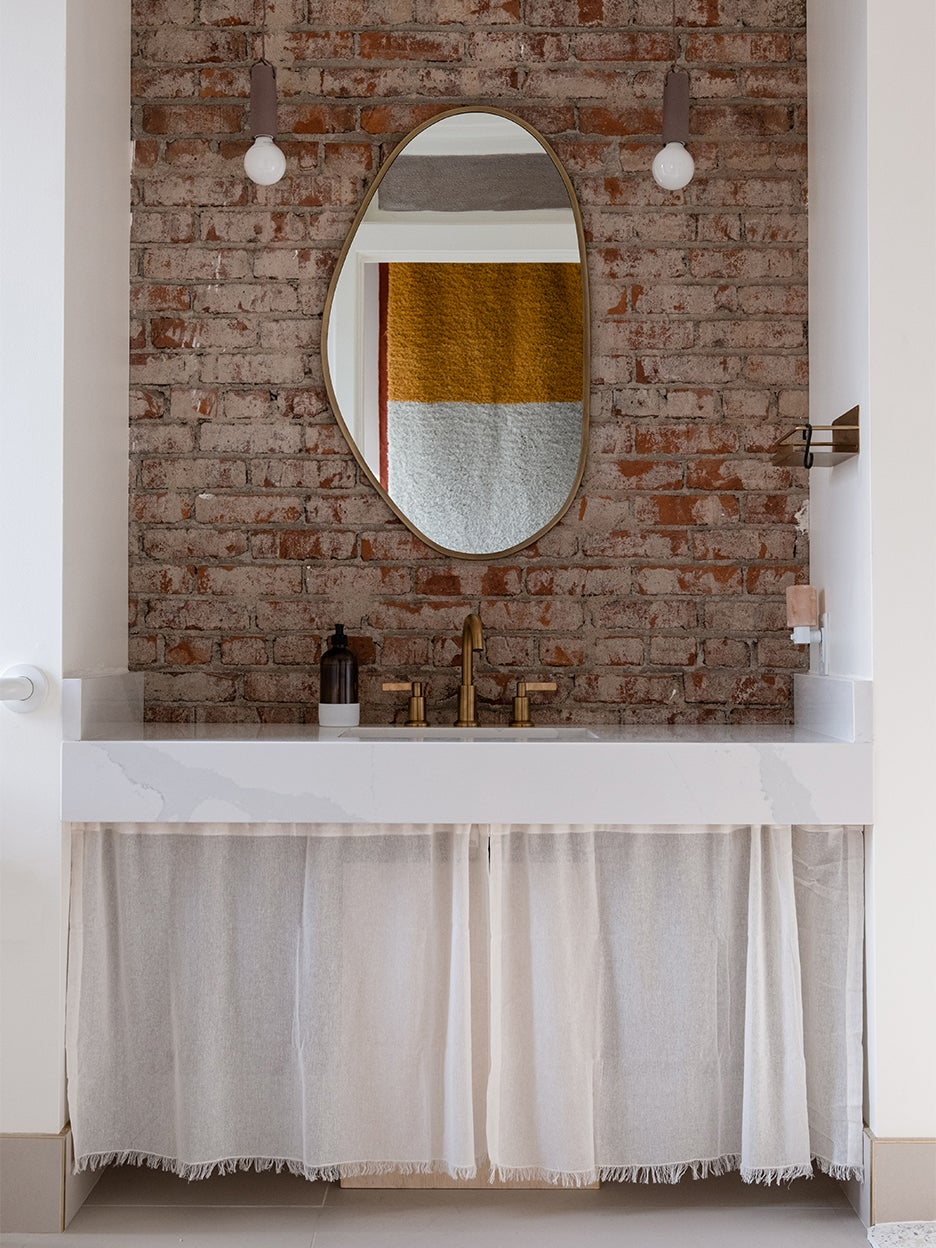 brick wall with oval mirror and sink skirt