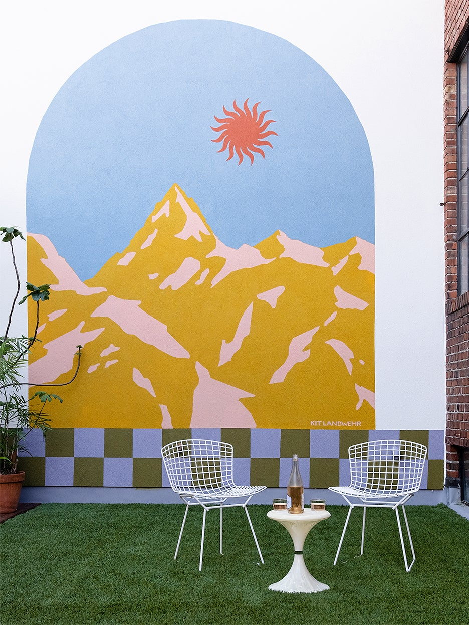 colorful mural of mountains and sun in courtyard