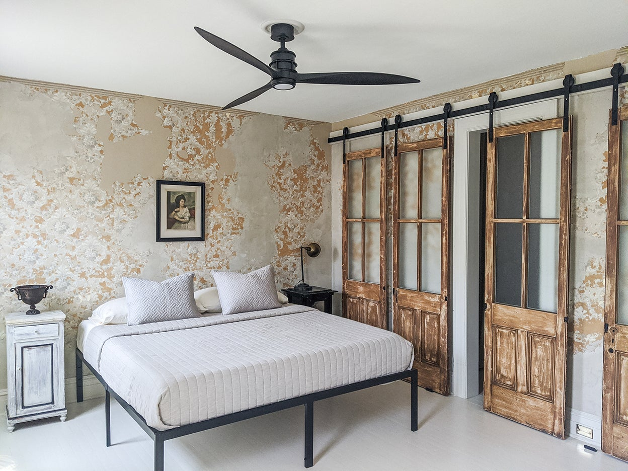 bedroom with black ceiling fan and white bedding