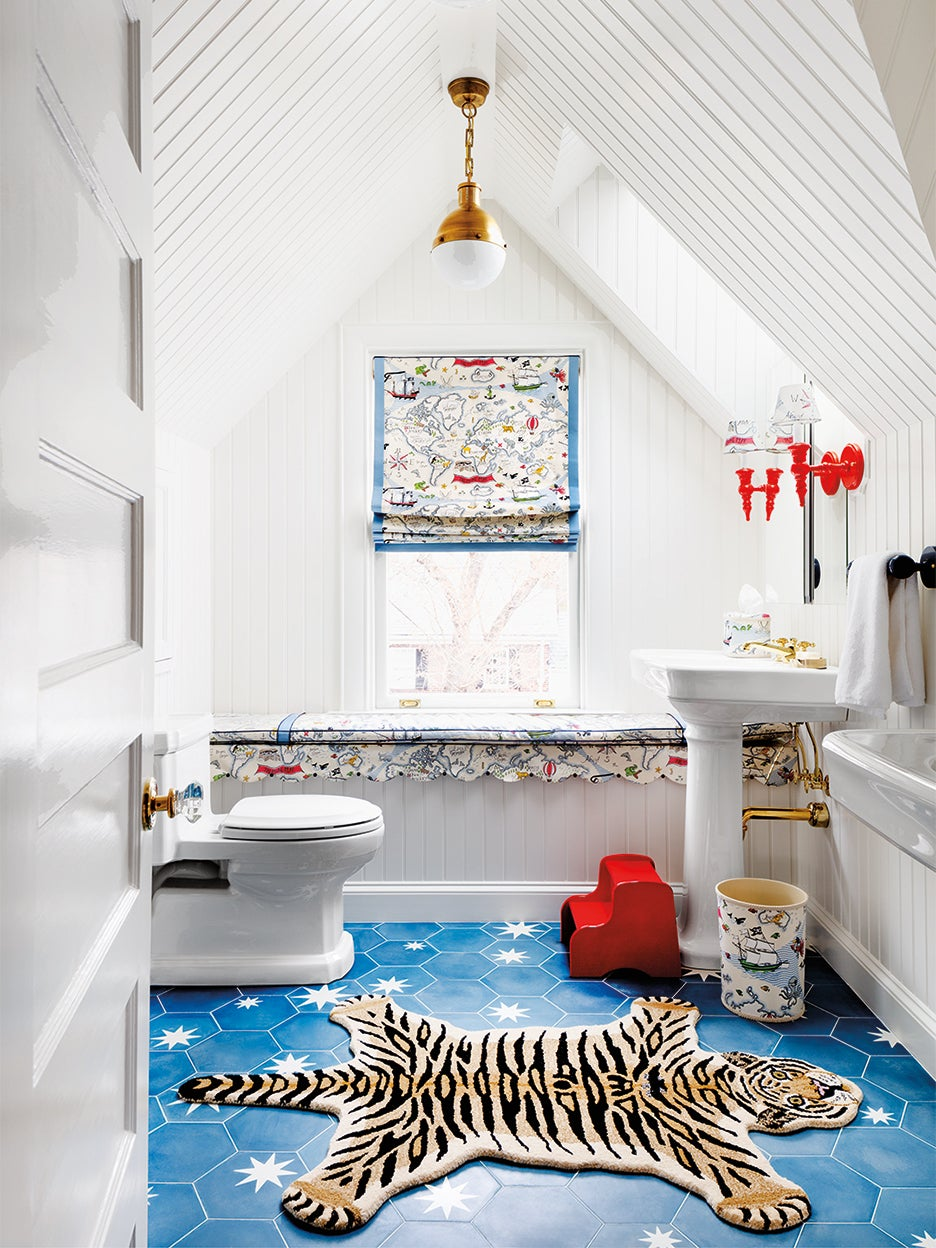 white kids bathroom with blue star floor tile and red sconces