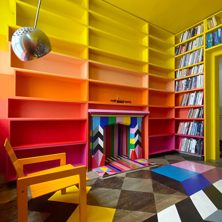 colorful library with ombre bookcases and floor mural