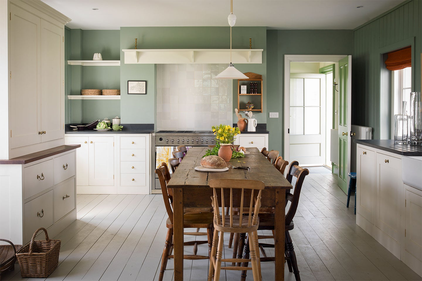 green kitchen with white cabinets and rustic dining table