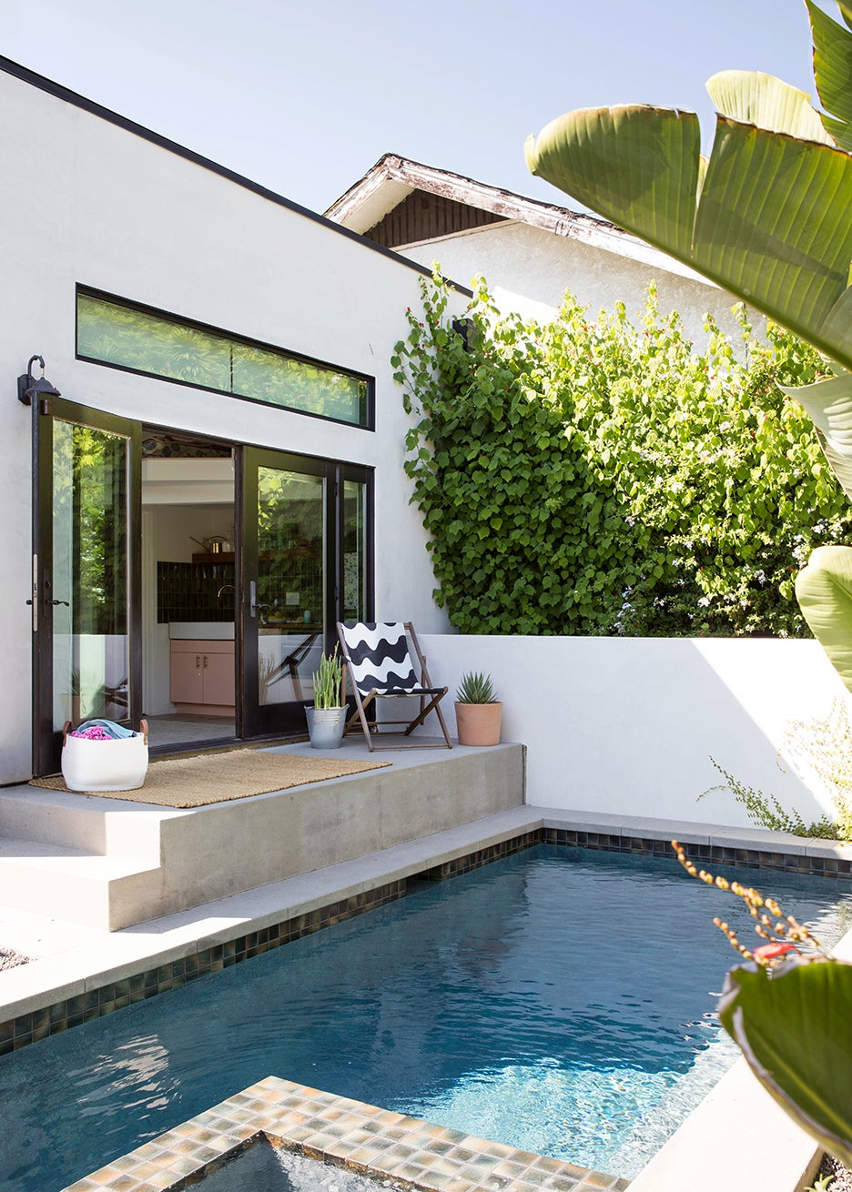 pool next to patio with lots of plants