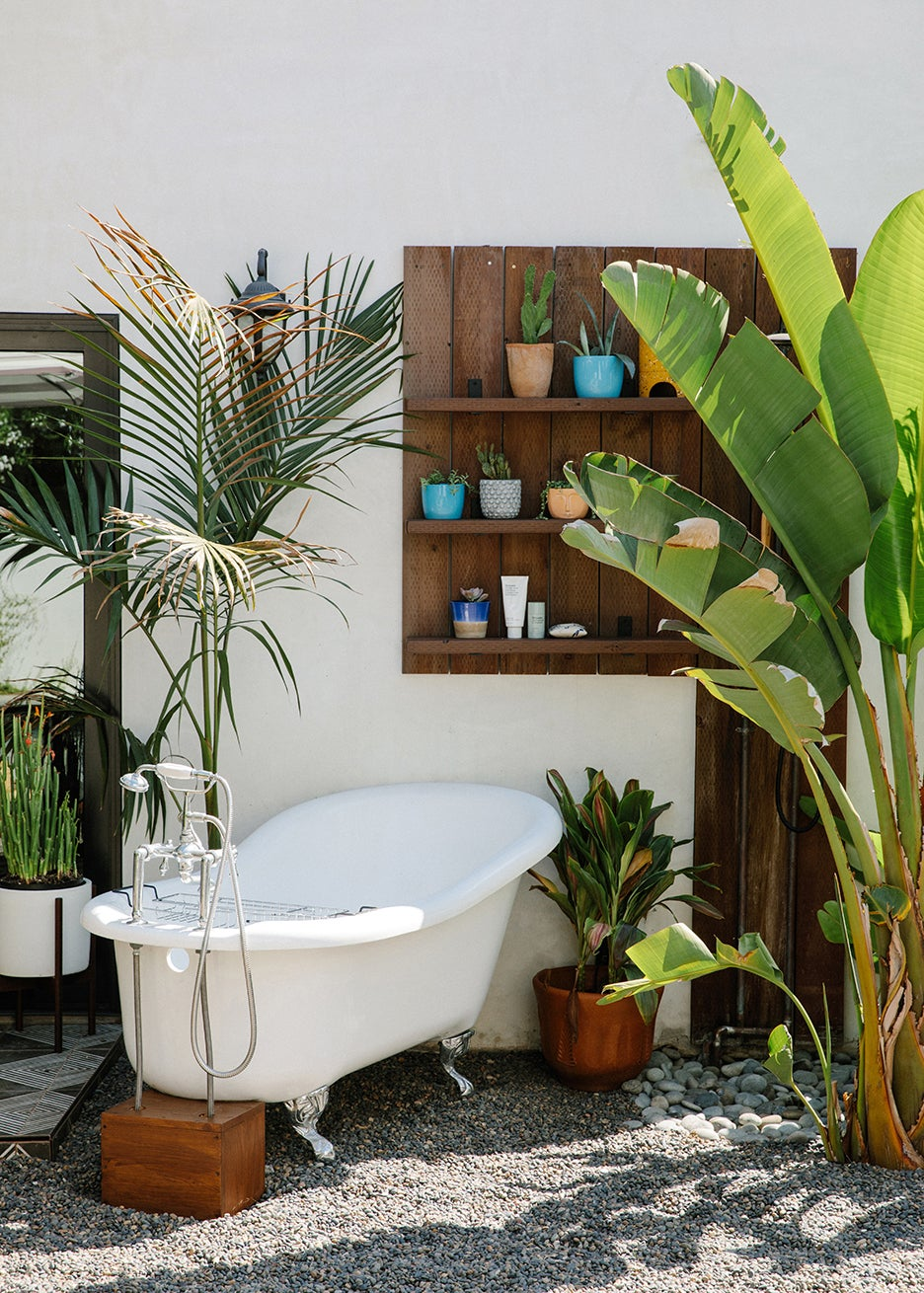 outdoor tub in front of bookcase with lots of pots