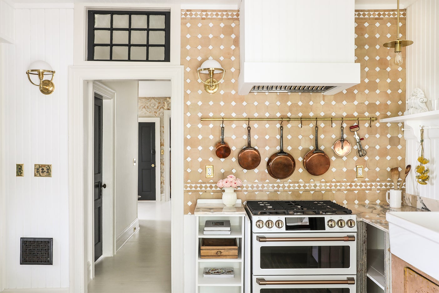 terracotta kitchen with copper pans above oven