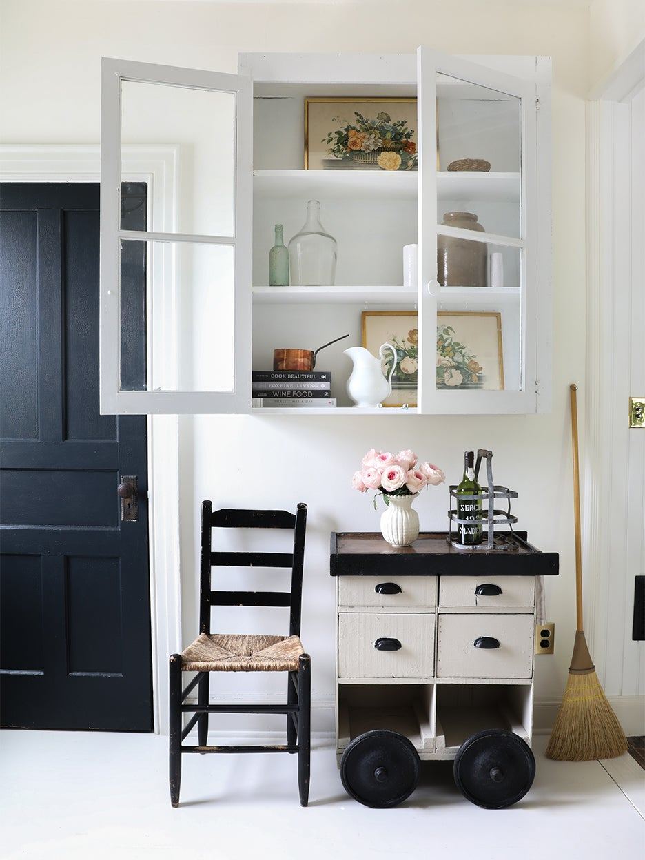 white room with glass front cabinet and black door