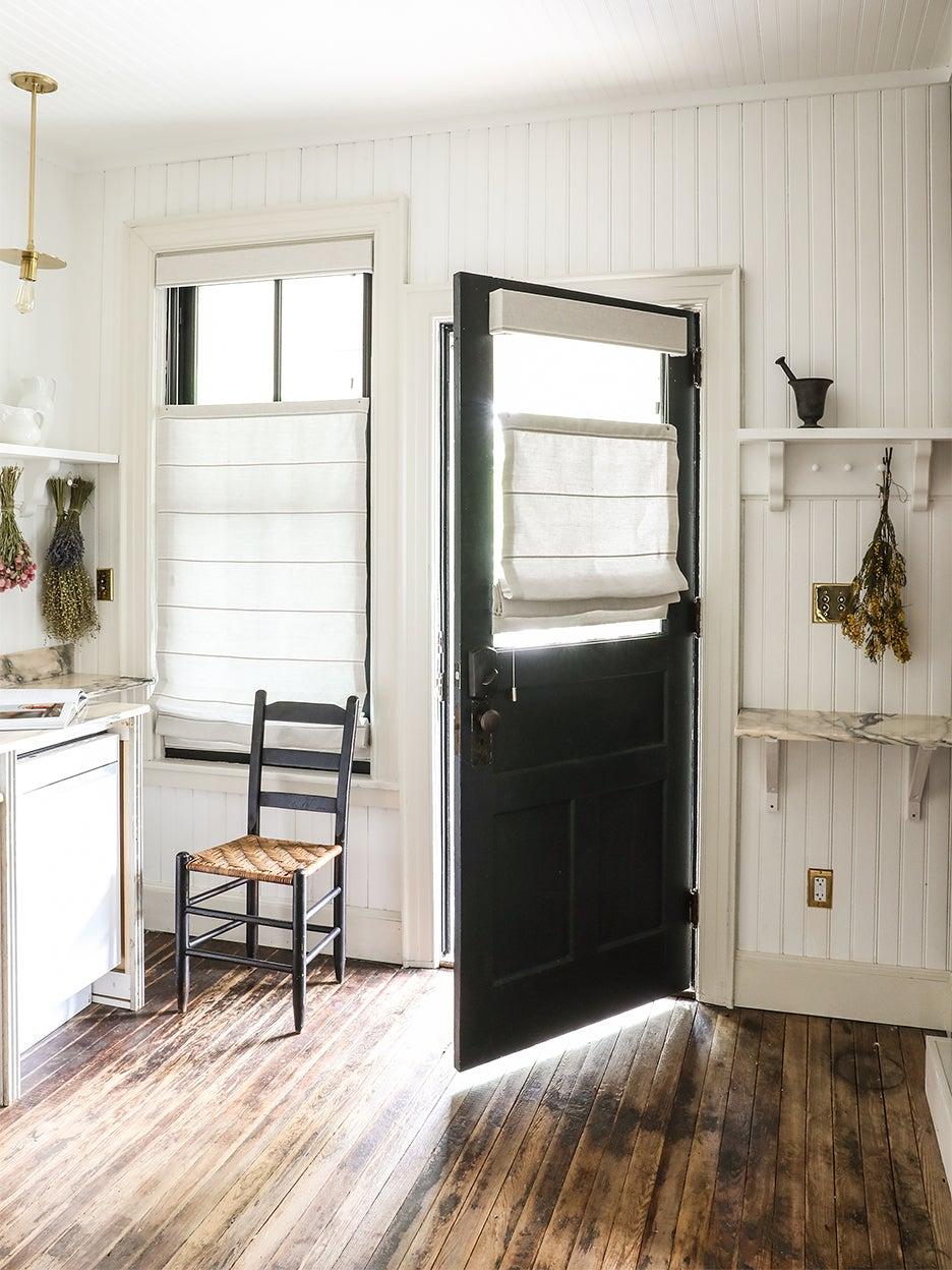 black door open in white kitchen