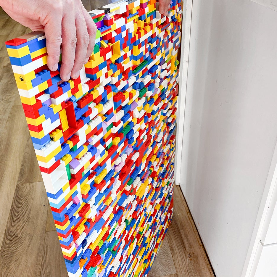 hand holding lego wall