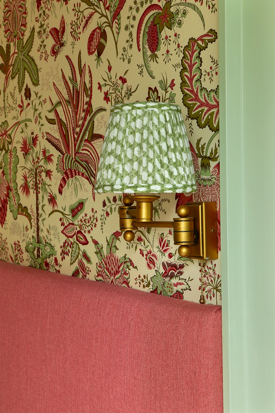 Floral fabric walls with brass sconce