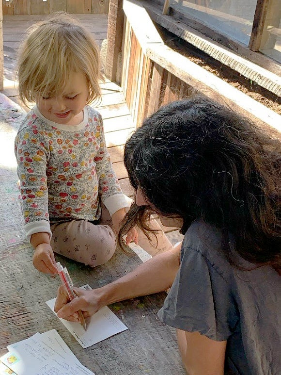 Mother and child writing a postcard