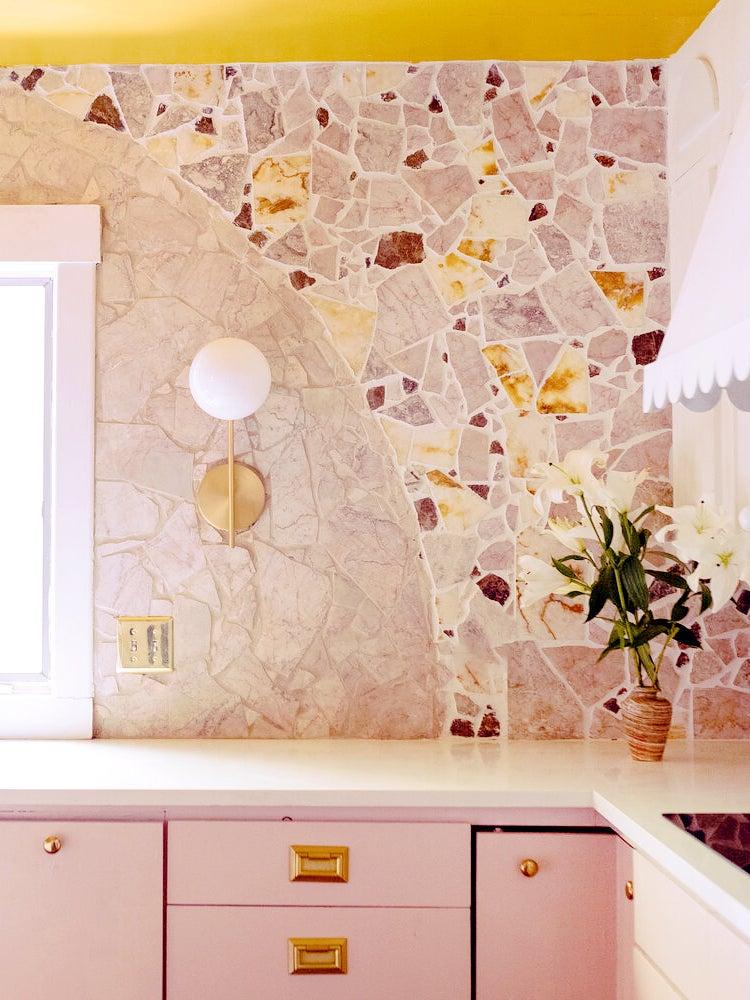 stone kitchen backsplash with pink cabinets
