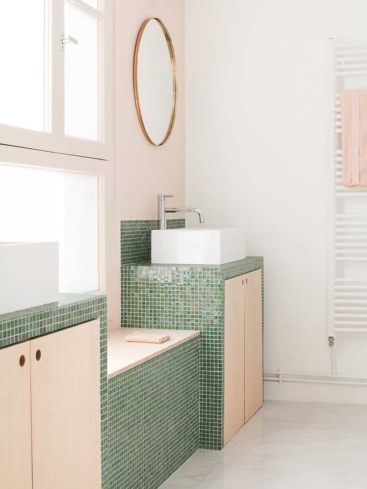 pink bathroom with small green tiles around the sink