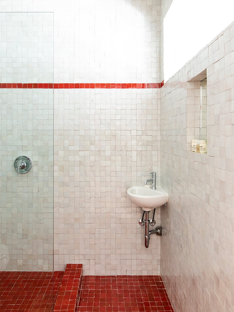 white zellige tile shower nook with strip of red tiles