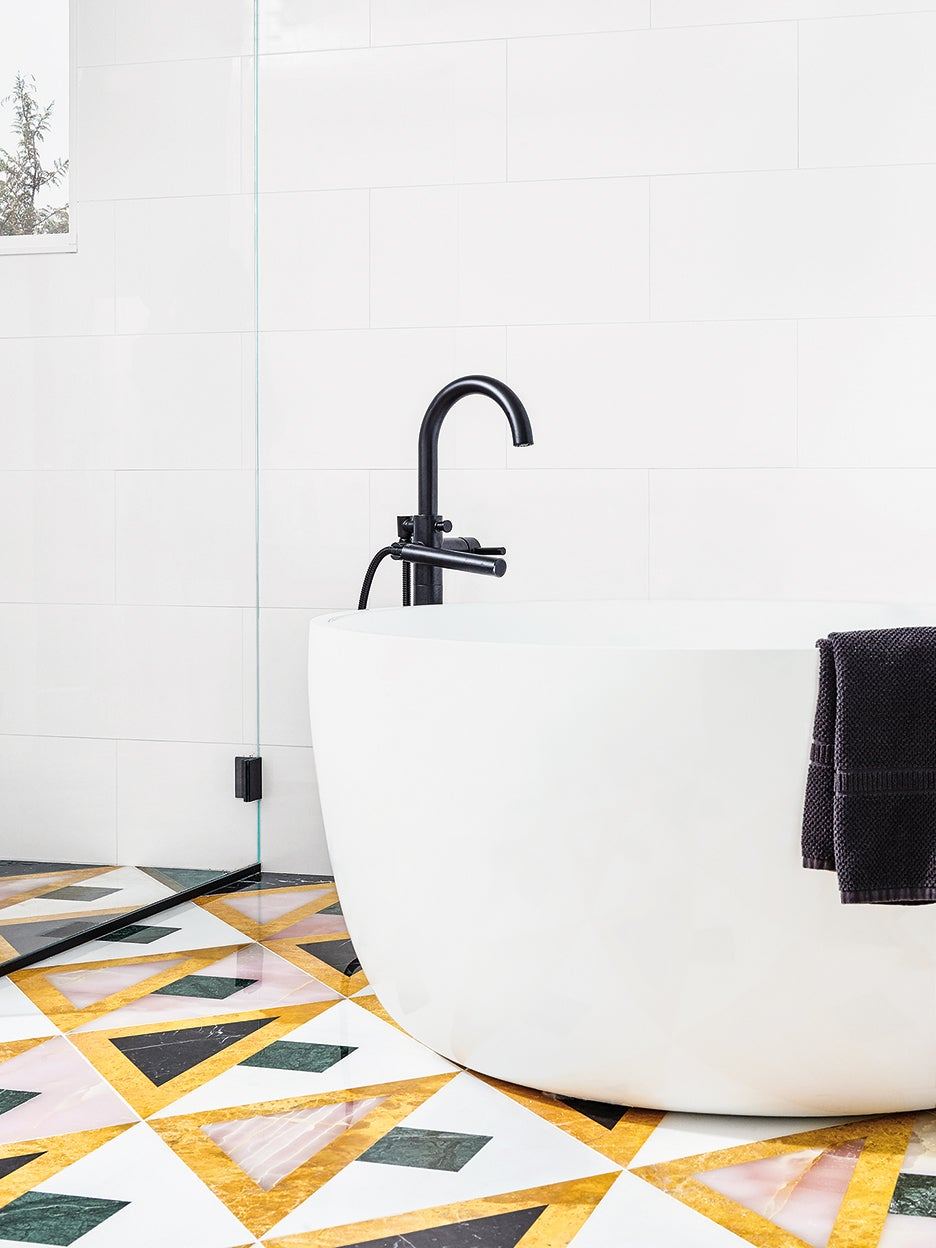 white bathroom with tub and colorful marble tile floor