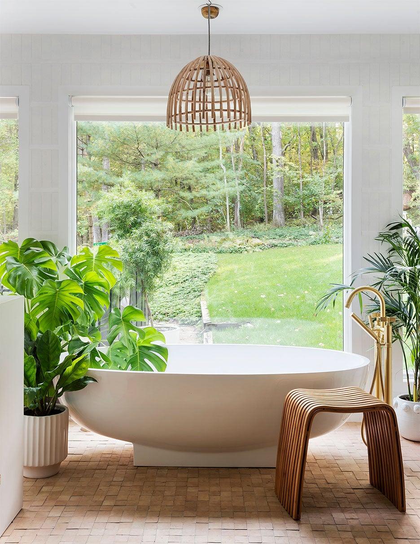 bathroom with huge window overlooking backyard, terracotta tiles, and white tub