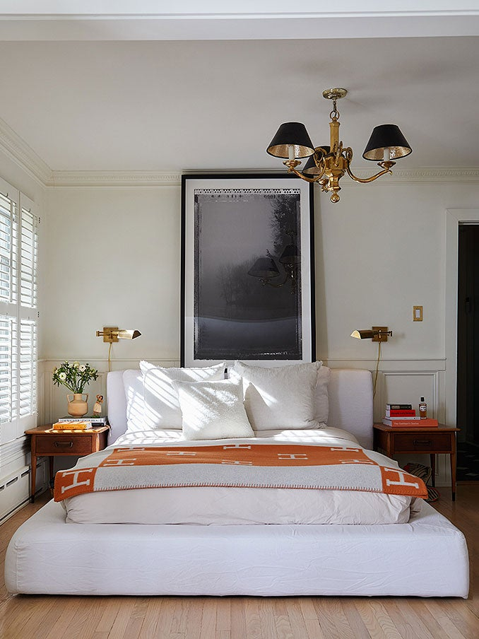 neutral bedroom with brass light pendant and Hermes blanket