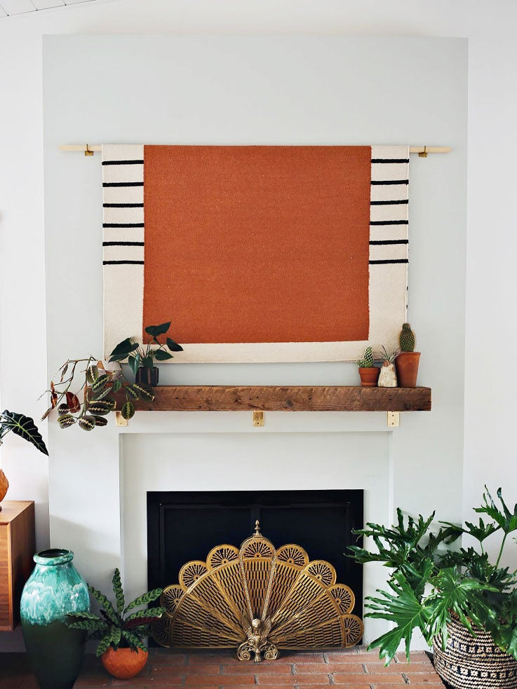 orange tapestry over fireplace