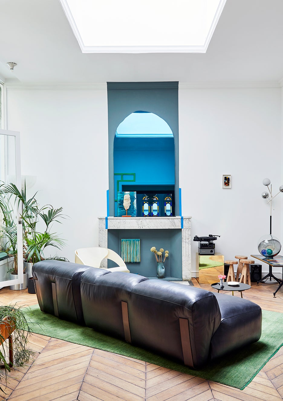 Black leather sofa placed diagonally above a green rug