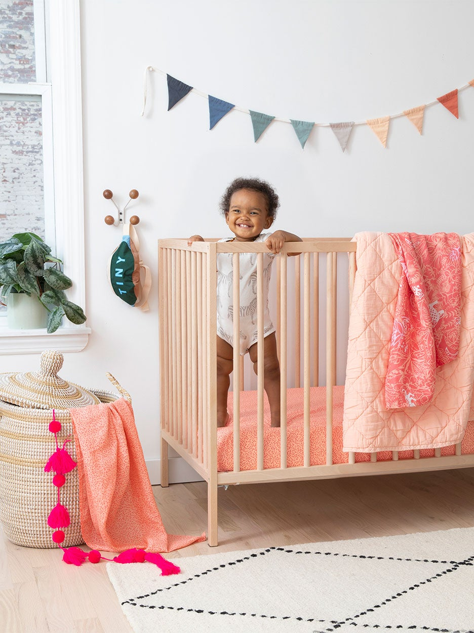 baby in crib with pink bedding