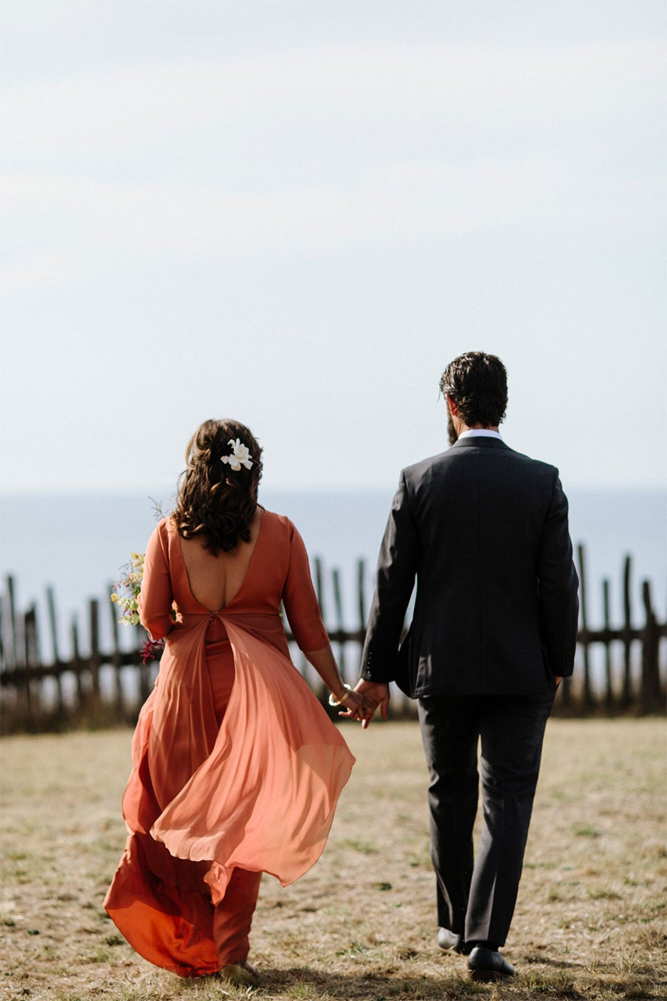 couple walking hand in hand towards fence