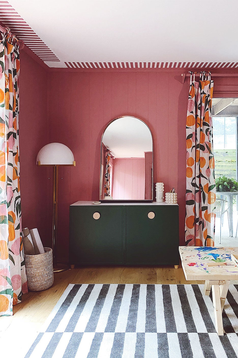 pink room with green cabinet and mirror