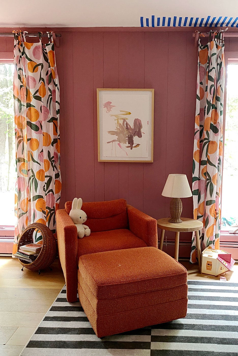 pink room with orange-printed curtains and orange armchair