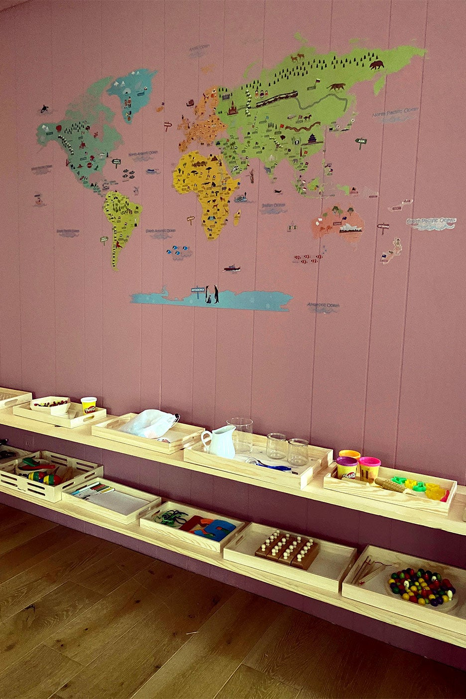 pink wall map decal and shelves with trays