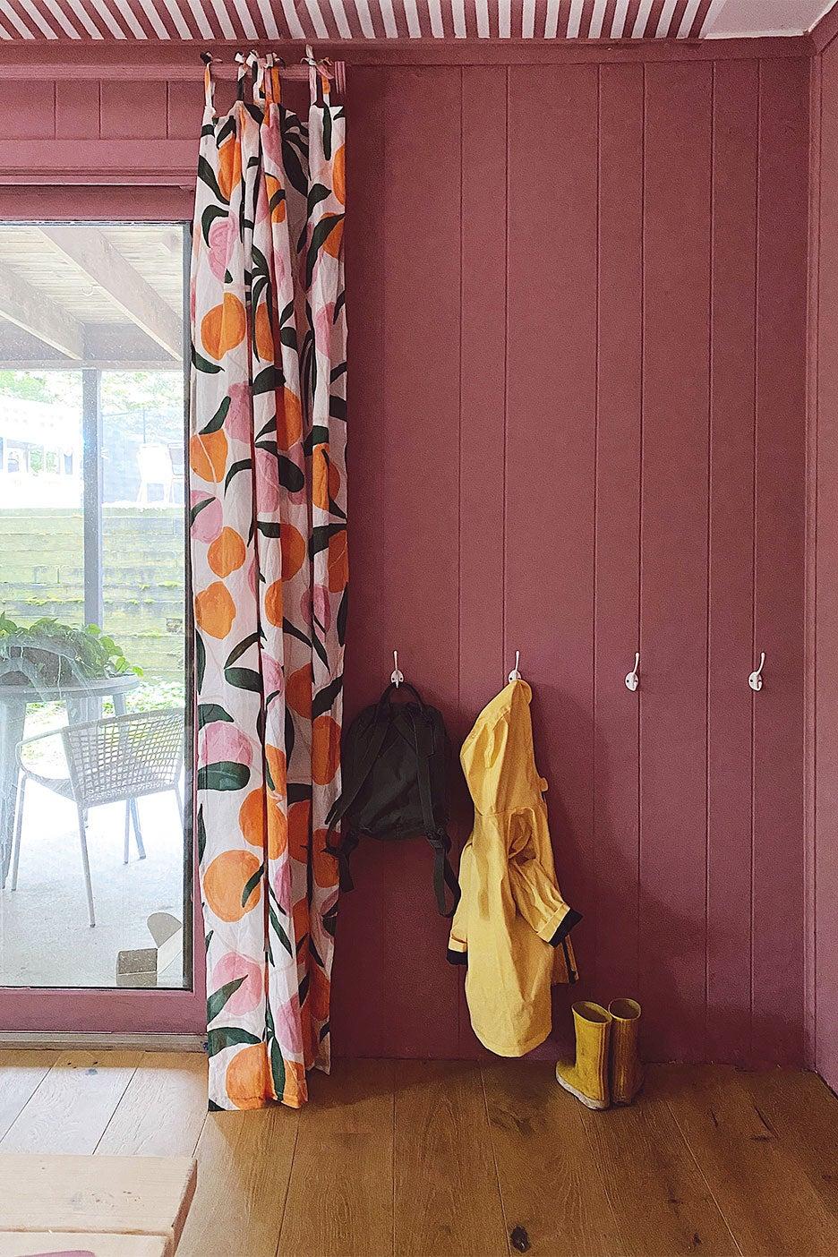 pink walls behind coat rack