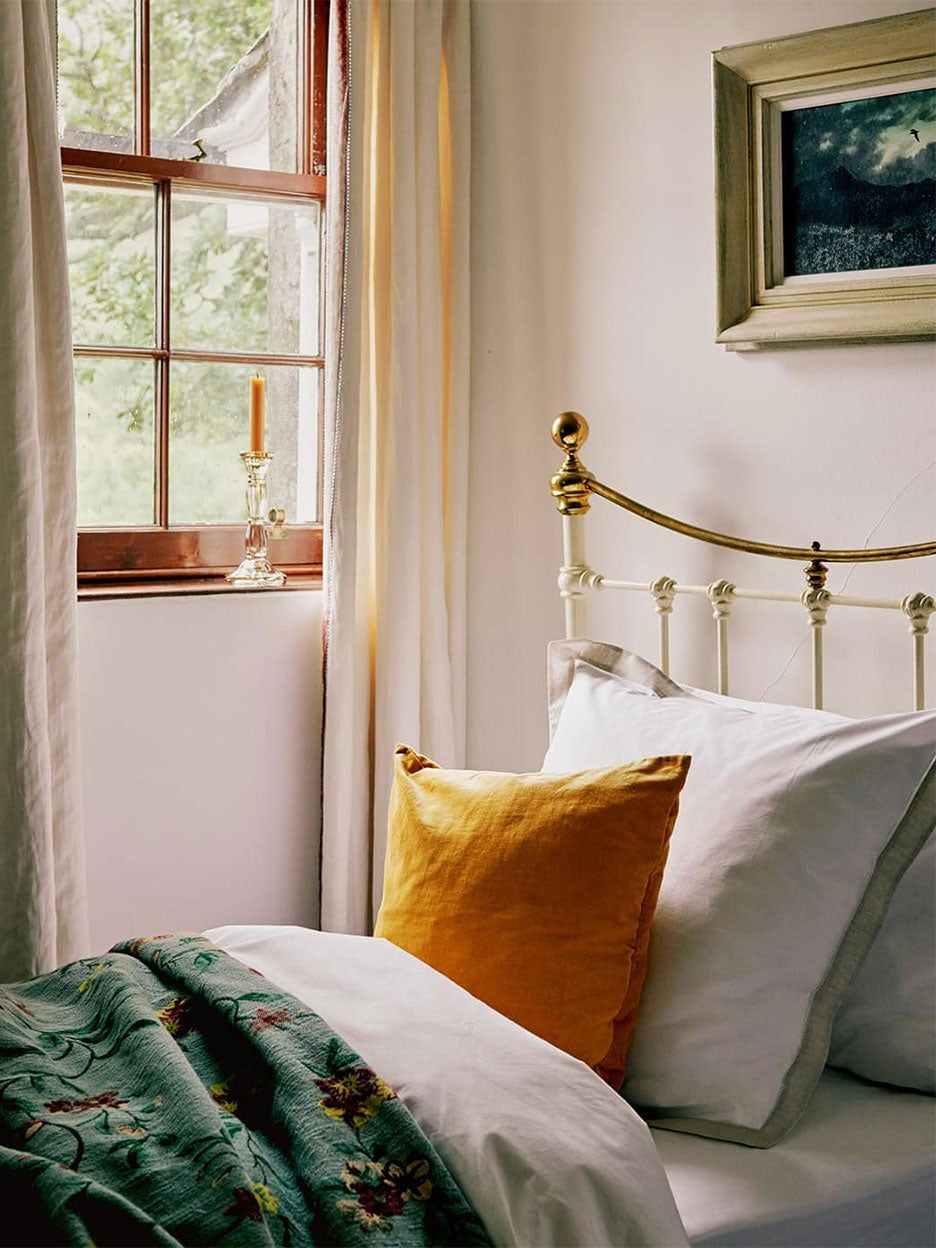 bedroom with ochre throw pillows and green bedding