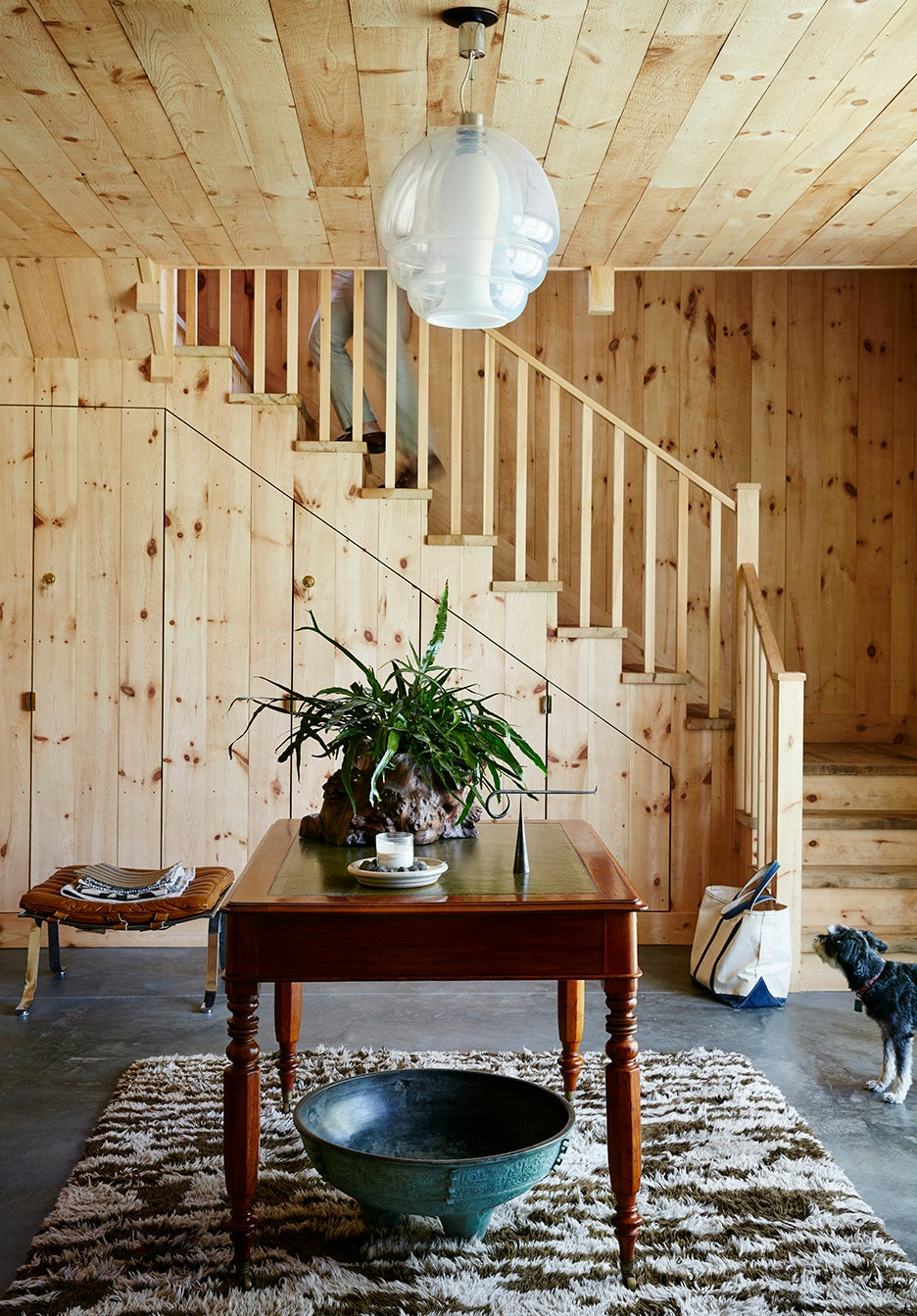 Wood-paneled mudroom with concrete floors