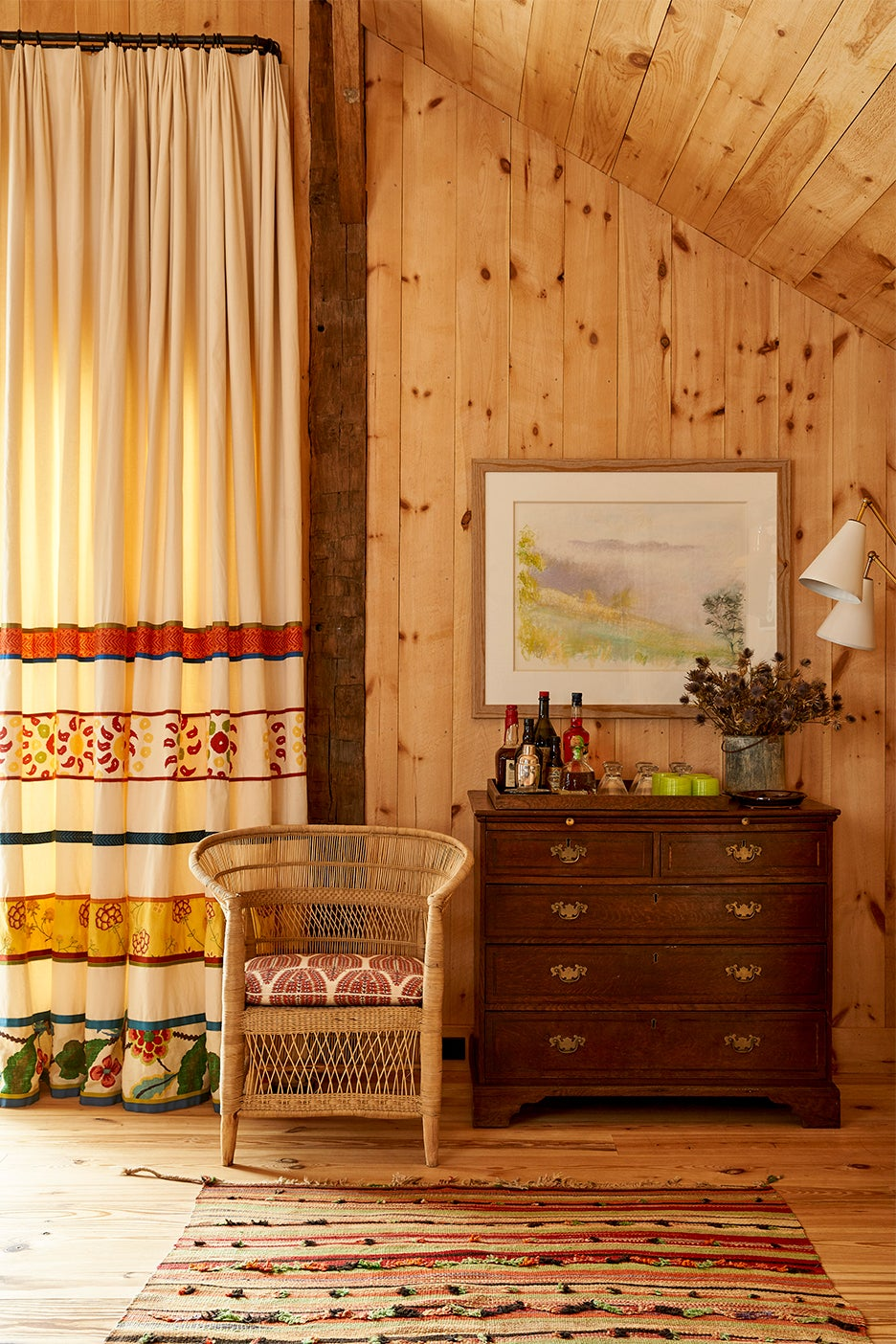 Woven chair and antique dresser in wood-paneled room