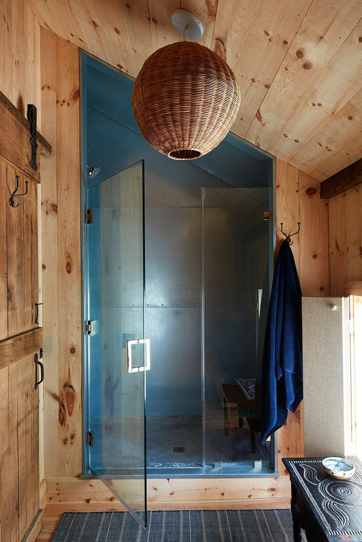 Wood-paneled bathroom with galvanized steel shower