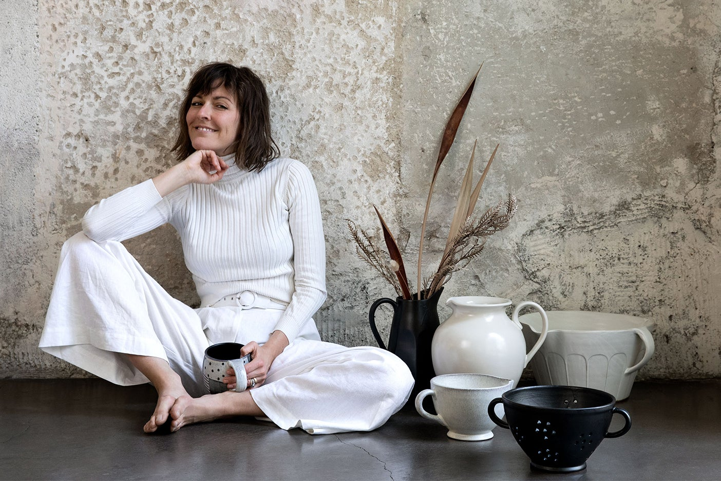 leanne ford in white outfit sitting near vessels