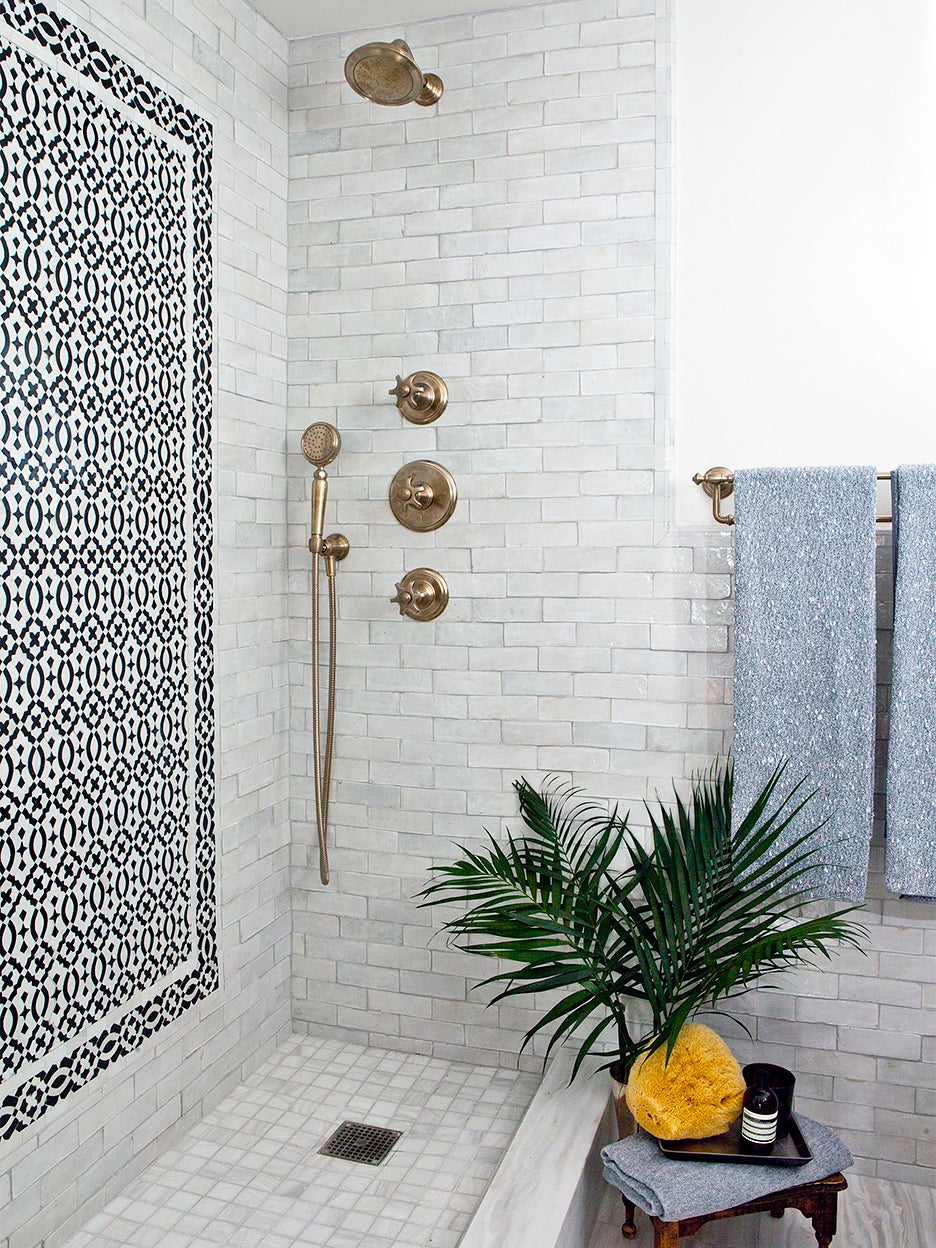 light gray tiled shower nook with black mosaic