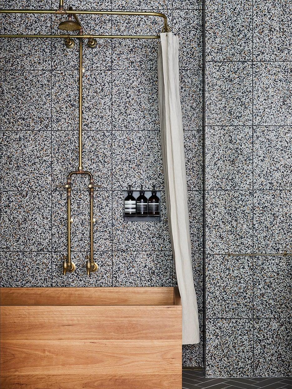 bathroom with wood tub and terrazzo walls