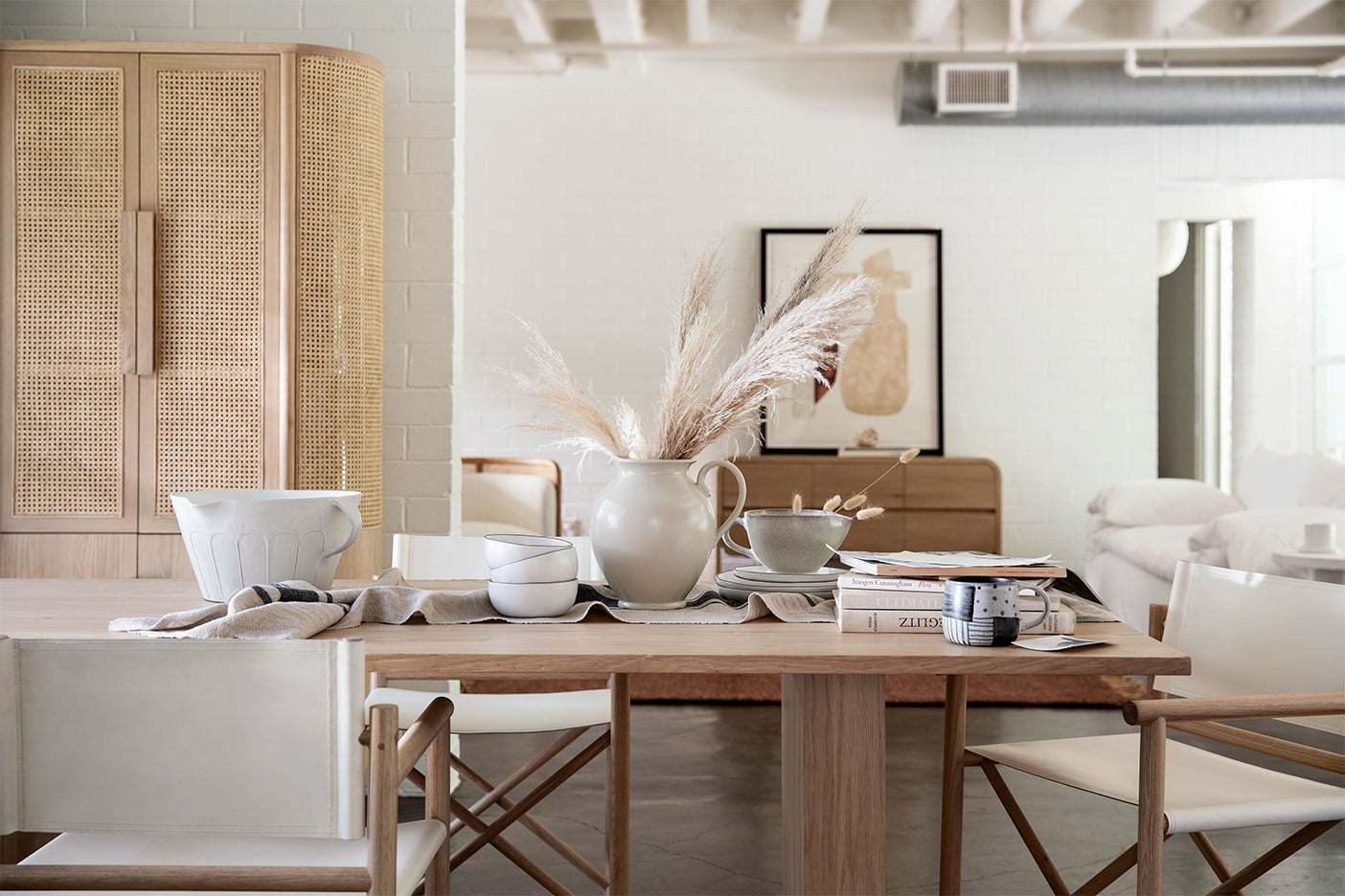 dining room table full of neutral-colored ceramics