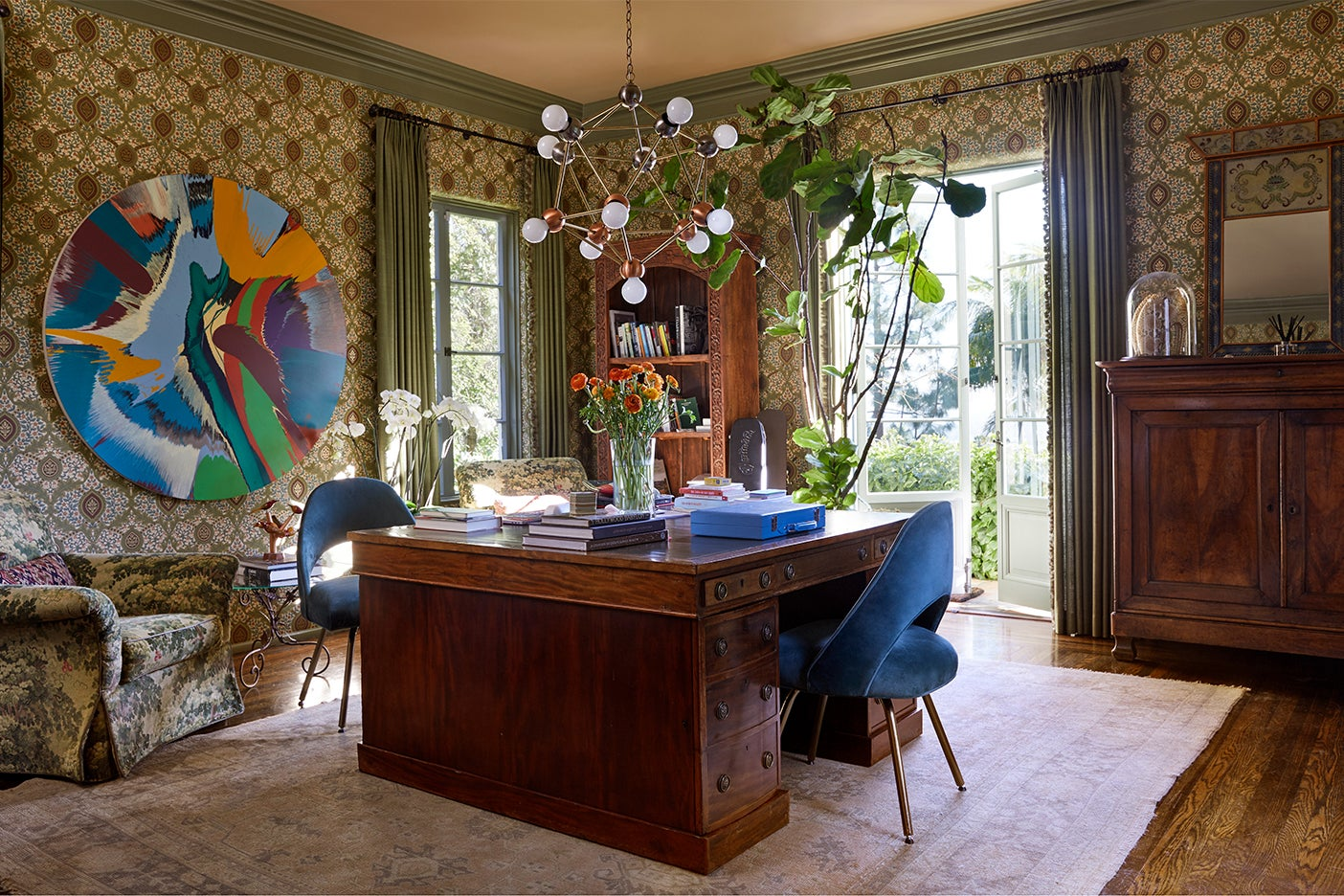 Office with blue desk chair and circular art