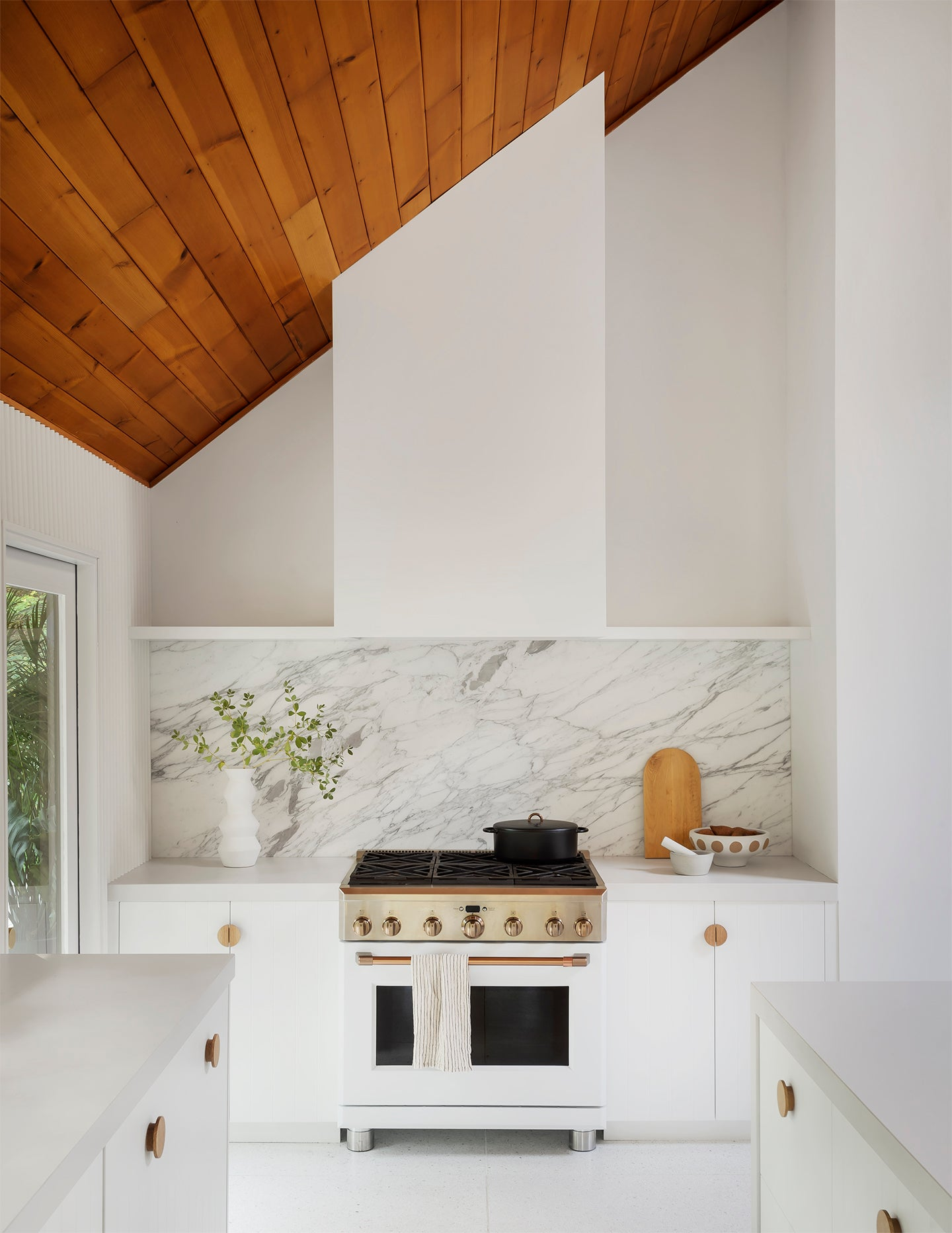 white kitchen with sloped wood ceiling