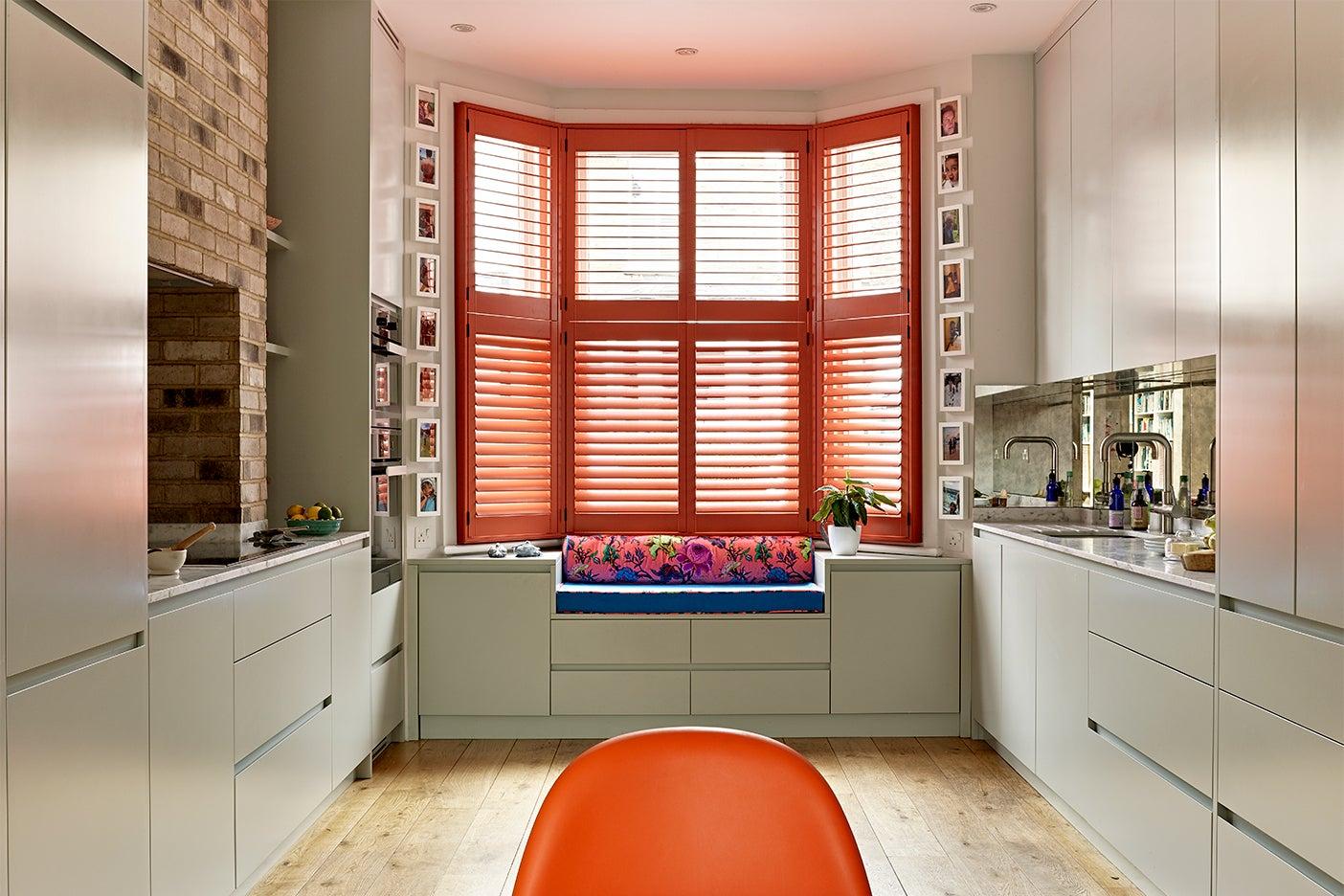 Kitchen window seat with orange shutters