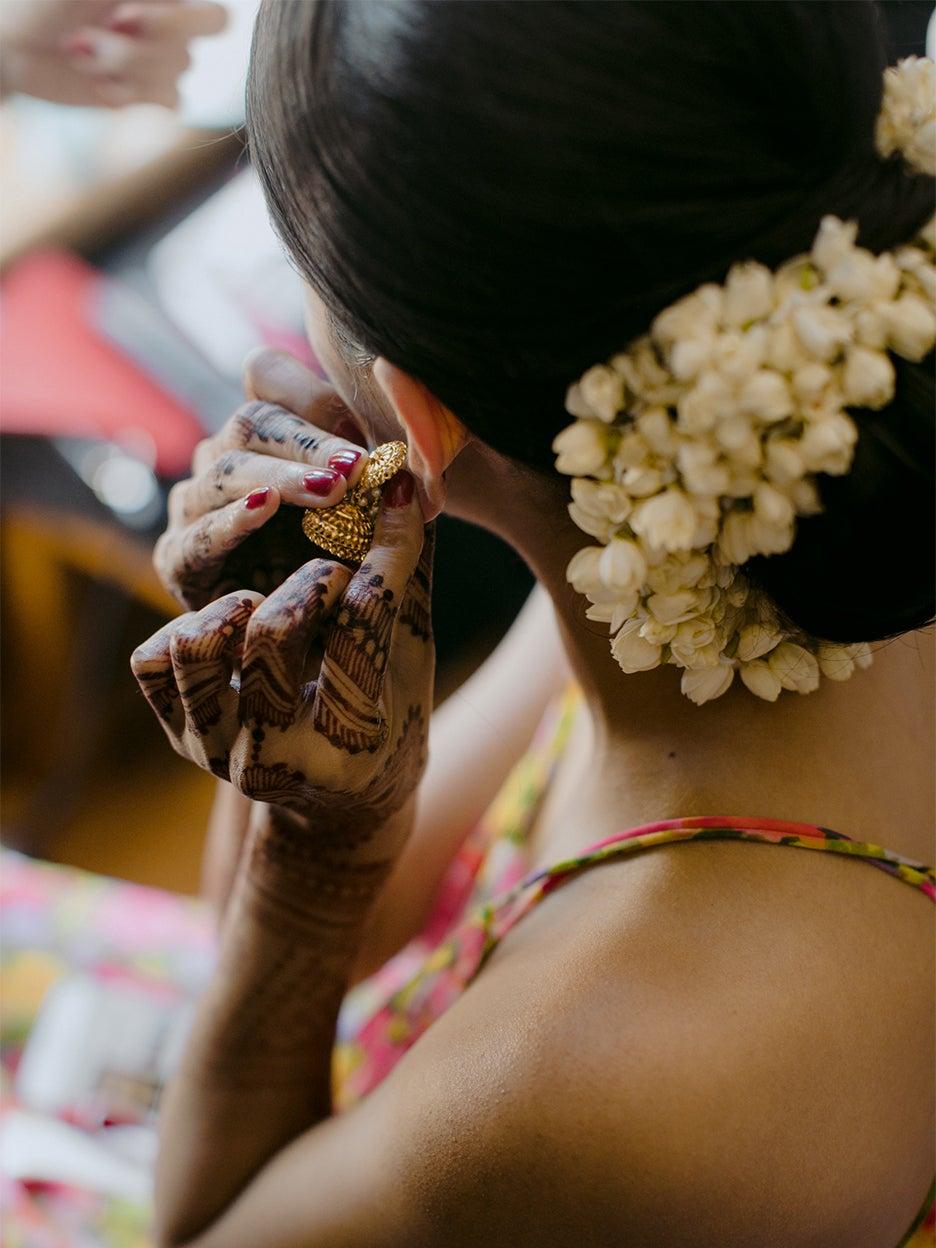 woman putting in earings