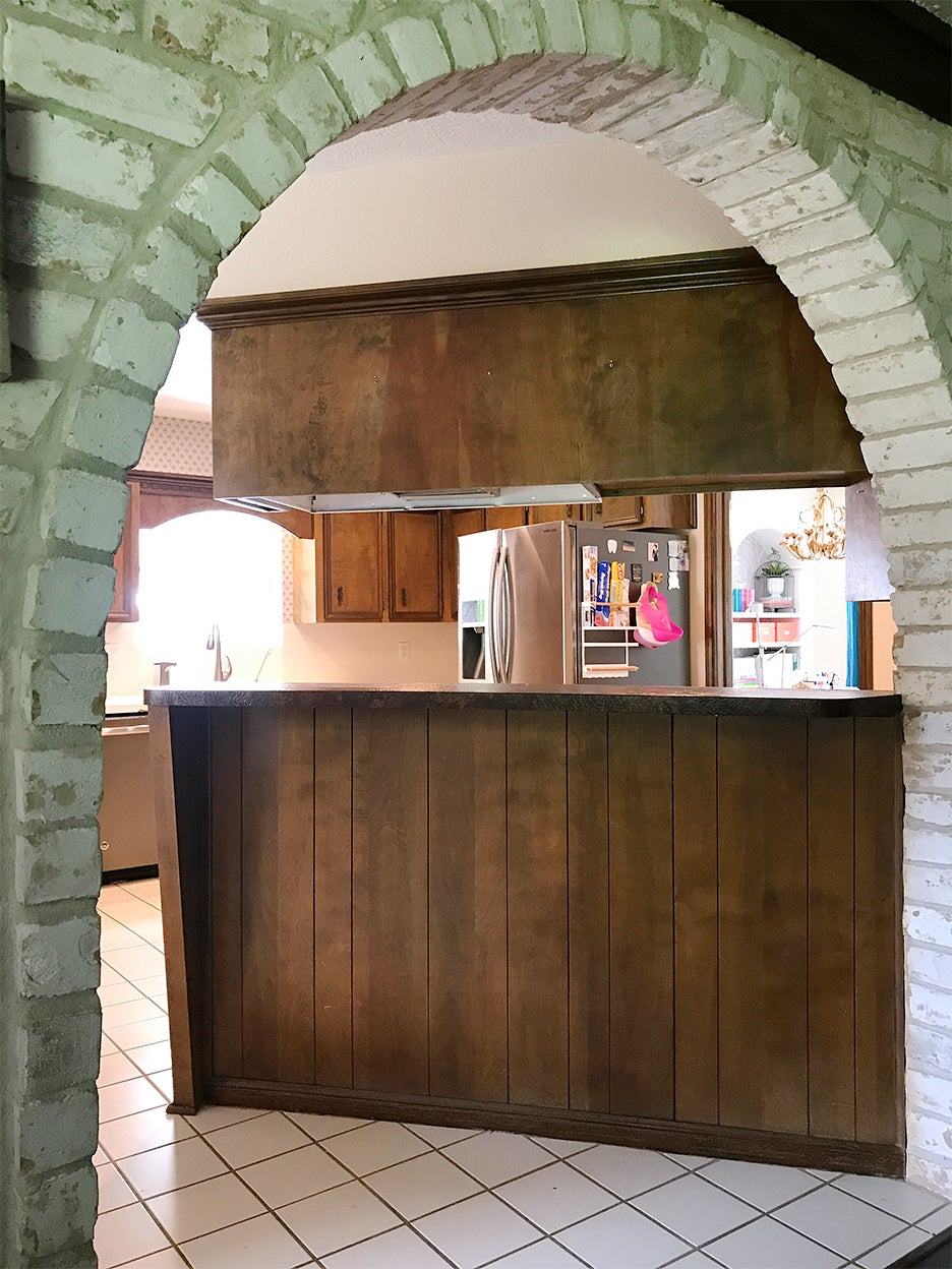 archway leading to brown kitchen